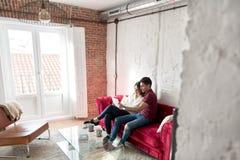 Giovani coppie felici rilassate a casa con un tabet fotografia stock libera da diritti