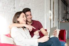 Giovani coppie felici rilassate a casa con un tabet fotografie stock libere da diritti