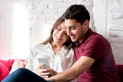 Giovani coppie felici rilassate a casa con un telefono cellulare fotografie stock libere da diritti