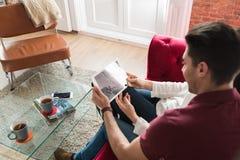 Giovani coppie felici rilassate a casa con una compressa fotografia stock libera da diritti