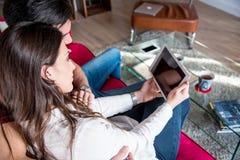 Giovani coppie felici rilassate a casa con una compressa immagine stock libera da diritti