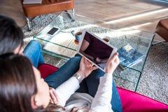 Giovani coppie felici rilassate a casa con una compressa immagini stock