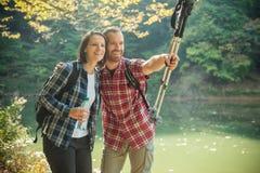 Giovani coppie felici sorridenti che fanno un'escursione lungo la riva del lago, abbracciantesi immagine stock