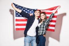 Giovani coppie felici sui precedenti della bandiera degli Stati Uniti Immagini Stock Libere da Diritti