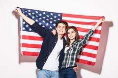 Giovani coppie felici sui precedenti della bandiera degli Stati Uniti Fotografia Stock