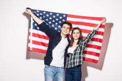 Giovani coppie felici sui precedenti della bandiera degli Stati Uniti Fotografie Stock Libere da Diritti