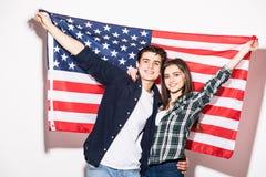 Giovani coppie felici sui precedenti della bandiera degli Stati Uniti Immagine Stock Libera da Diritti