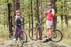 Giovani coppie felici sulle bici che esaminano macchina fotografica con i pollici su immagine stock