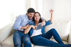 Giovani coppie felici sullo strato a casa che gode per mezzo del computer digitale della compressa Immagini Stock
