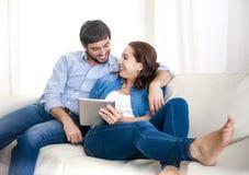 Giovani coppie felici sullo strato a casa che gode per mezzo del computer digitale della compressa Fotografie Stock
