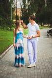 Giovani coppie incinte nel parco di estate immagine stock