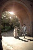 Giovani coppie indiane felici che passeggiano attraverso l'arco del mattone Fotografia Stock