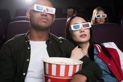 giovani coppie interrazziali in vetri 3d con il film di sorveglianza del popcorn Immagini Stock
