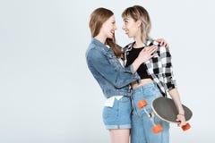 Giovani coppie lesbiche che posano insieme al pattino isolato su grey Fotografie Stock