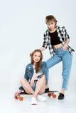 Giovani coppie lesbiche che posano insieme al pattino isolato su grey Fotografia Stock