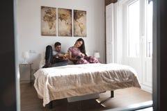 Giovani coppie a letto intrattenute con il libro e un coniglietto fotografia stock