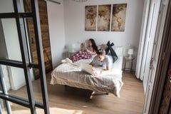 Giovani coppie a letto intrattenute sul loro computer e compressa immagine stock
