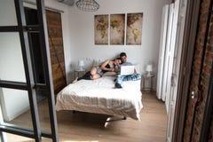 Giovani coppie a letto intrattenute sul loro computer e compressa immagini stock