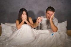 Giovani coppie a letto spaventate e sollecitate dopo il risultato positivo sul test di gravidanza con la donna incinta che preved fotografia stock