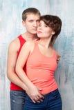 Giovani coppie in magliette rosse vicino alla parete Immagine Stock