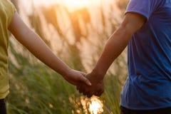 Giovani coppie in mano della tenuta di amore e camminare al parco durante il sole fotografia stock libera da diritti