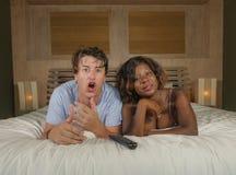 Giovani coppie miste felici ed attraenti di etnia con la bella donna afroamericana nera e l'uomo bianco sorpreso a casa che si tr immagine stock libera da diritti