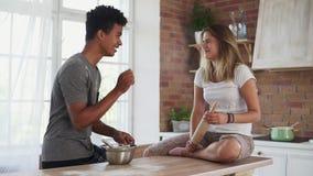 Giovani coppie multietniche che cucinano insieme nella cucina Ingredienti africani attraenti di miscelazione dell'uomo in un vaso video d archivio