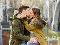 Giovani coppie nell'amore che bacia tenero sulla via che celebra giorno o anniversario di biglietti di S. Valentino che incoraggi Immagine Stock Libera da Diritti
