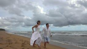 Giovani coppie nell'amore che corre lungo la spiaggia vuota dell'oceano al tramonto, tenentesi per mano stock footage
