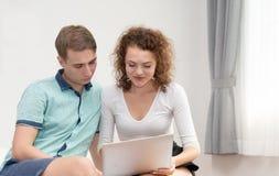 Giovani coppie nell'amore che relexing e che utilizza con il computer portatile nel salone fotografie stock