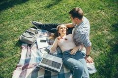 Giovani coppie nell'amore che riposa sul prato inglese dopo lo studio fotografia stock libera da diritti