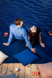 Giovani coppie nell'amore che si rilassa sul terrazzo vicino all'acqua Fotografia Stock