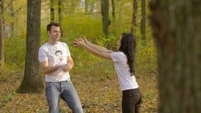 Giovani coppie nell'amore nel parco di autunno Gioco delle donne e degli uomini con le mele archivi video