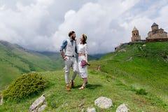 Giovani coppie nell'amore, stringere a sé, in un uomo in un vestito ed in ragazza nel bianco con i fiori, Fotografia Stock