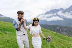 Giovani coppie nell'amore, stringere a sé, in un uomo in un vestito ed in ragazza nel bianco con i fiori, Fotografie Stock Libere da Diritti