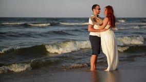 Giovani coppie nell'amore sulla spiaggia Belle coppie in vestiti bianchi Amanti che si tengono per mano e che abbracciano stock footage