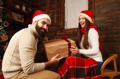 Giovani coppie nella casa delle vacanze in regali dei regali di Natale Fotografia Stock