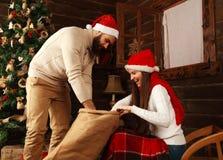 Giovani coppie nella casa delle vacanze in regali dei regali di Natale Immagini Stock Libere da Diritti