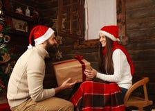 Giovani coppie nella casa delle vacanze in regali dei regali di Natale Immagini Stock