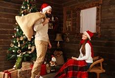Giovani coppie nella casa delle vacanze in regali dei regali di Natale Fotografia Stock Libera da Diritti