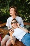Giovani coppie nella musica d'ascolto delle cuffie mentre spendendo tempo in parco Ragazzo premuroso che si siede sul banco e vag immagine stock libera da diritti