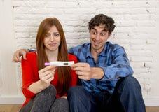 Giovani coppie nella scossa e sorpresa con la gravidanza positiva rosa leggente spaventata della ragazza incinta fotografie stock