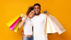 Giovani coppie nere con i sacchetti della spesa e la carta di credito fotografia stock libera da diritti