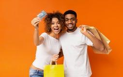 Giovani coppie nere con i sacchetti della spesa e la carta di credito fotografia stock