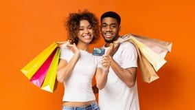 Giovani coppie nere con i sacchetti della spesa e la carta di credito immagine stock libera da diritti