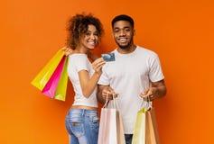 Giovani coppie nere con i sacchetti della spesa e la carta di credito fotografie stock