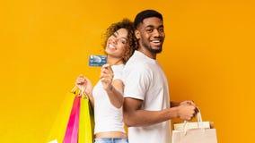Giovani coppie nere con i sacchetti della spesa e la carta di credito immagini stock libere da diritti