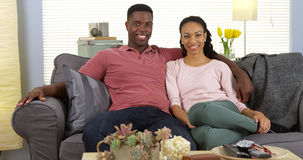 Giovani coppie nere felici che si rilassano sullo strato che esamina macchina fotografica Fotografia Stock Libera da Diritti