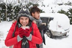 Giovani coppie in neve con l'automobile Immagini Stock Libere da Diritti