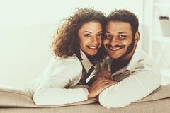 Giovani coppie pakistane che si siedono sul sofà e sull'abbracciare immagini stock libere da diritti